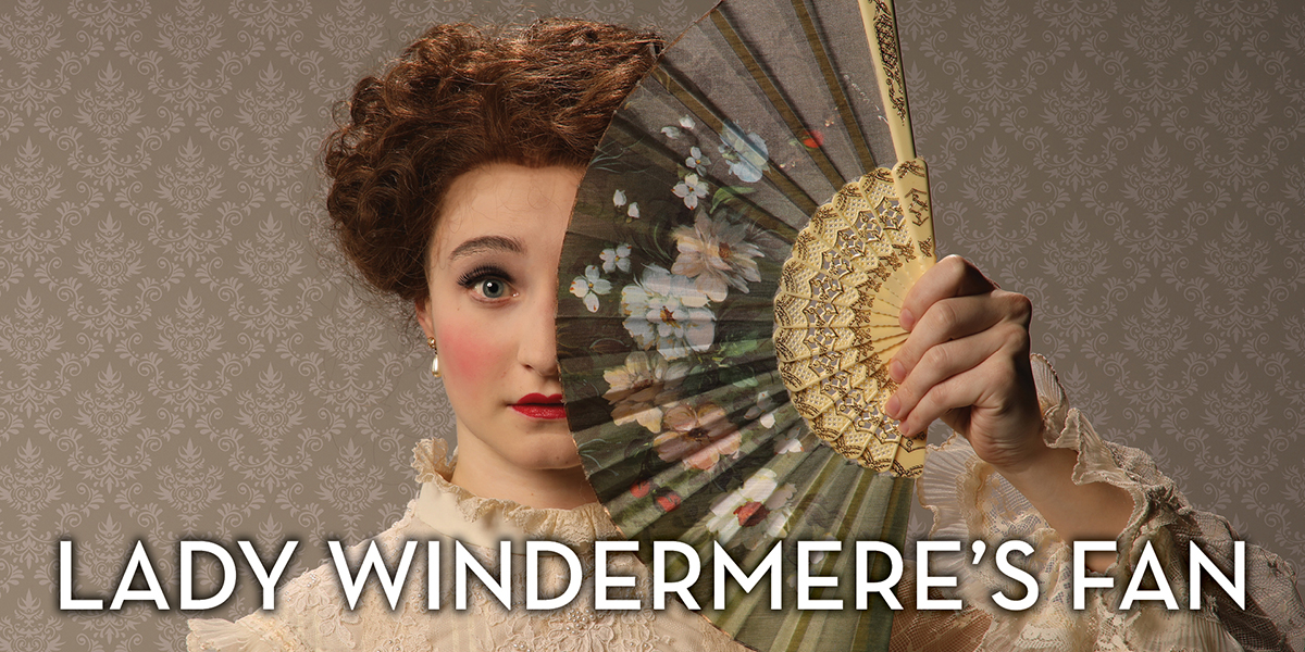 A woman in Edwardian dress holding a fan in front of her face in a promotional image for the play 'Lady Windermere's Fan.' Photo by Mark Lyons.