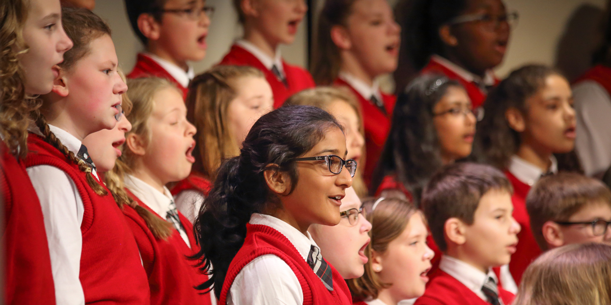 Children in the Cincinnati Youth Choir Allegro Choir perform on stage.