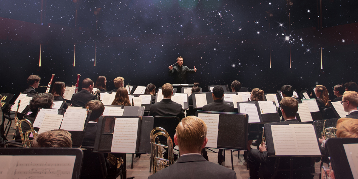 Kevin Holzman leads the CCM Wind Symphony in rehearsals. An image from space is superimposed in the background. Photo by Andrew Higley.