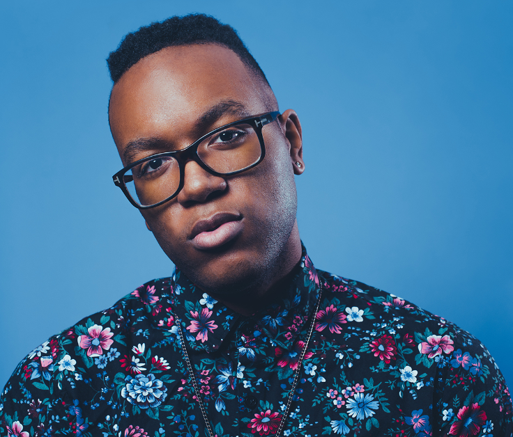 Jazz musician Michael Mayo, African American man, wearing black-rimmed glasses and a purple and blue hued floral shirt. He is standing in front of a blue background.