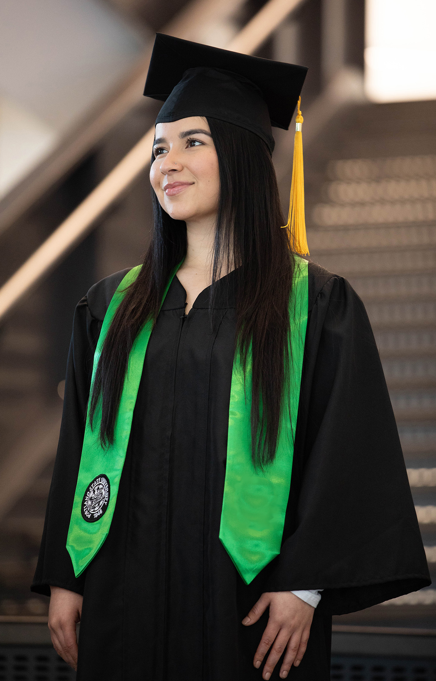 Stole of gratitude in Portland State green with circular commencement seal, worn by student in cap and gown.